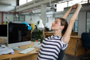 オフィスで伸びする女性
